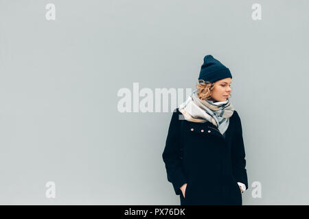 Female wearing coat, beanie hat and scarf, looking down, copy space. Young woman standing outdoors in cold weather on blue solid wall background. - Stock Photo