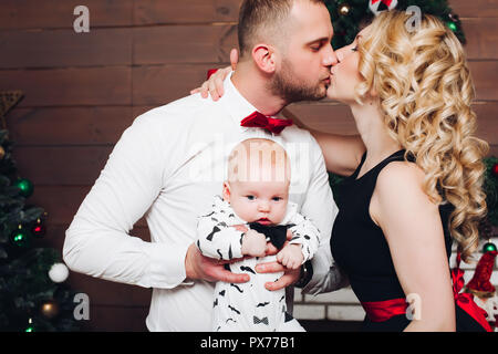 Elegance family standing together near fireplace, hugging son and kissing. - Stock Photo