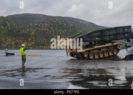 U.S. Marines with Combat Logistics Battalion 251, 2nd Marine Logistics Group-Forward, disembark an armored vehicle launched bridge from the USNS 1st Lt. Baldomero Lopez (T-AK 3010) in Norway, Oct. 8, 2018. U.S. Marine Corps, U.S. Navy, and Norwegian service members and civilians unloaded and inspected the equipment for Exercise Trident Juncture 18. Trident Juncture 18 enhances the U.S. and NATO Allies' and partners' abilities to work together collectively to conduct military operations under challenging conditions. (U.S. Marine Corps photo by Sgt. Bethanie C. Sahms) - Stock Photo