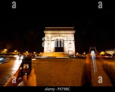 Tourist Taking Pictures of the Arc the Triumph with their phones - Stock Photo