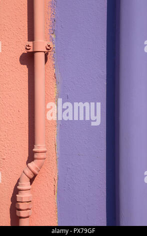 wall of a typical Burano Island house divided in half and painted in orange and purple - Stock Photo