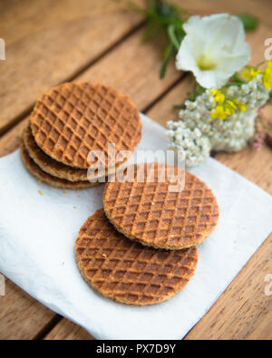 Traditional Dutch Stroopwafels syrup filled waffle cookies in setting with flowers - Stock Photo