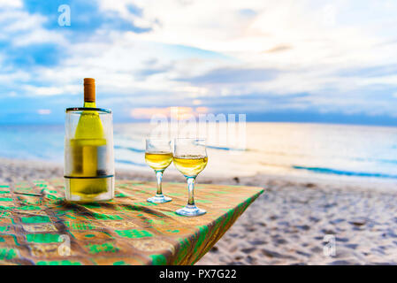 A bottle of wine and two glasses against the sea in Moalboal, Cebu, Philippines. With selective focus - Stock Photo