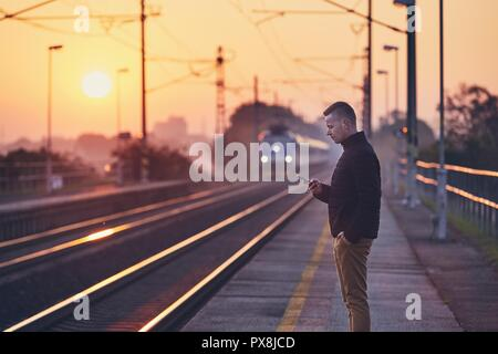 Young man waiting at railroad station platform and using smart phone against commuting train at sunrise. - Stock Photo