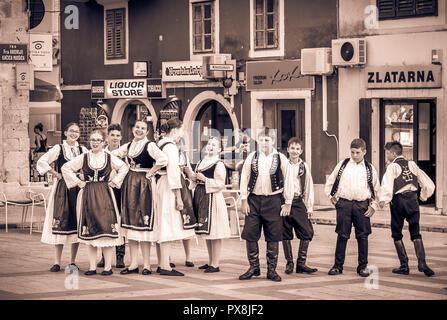 MAKARSKA, CROATIA - JULY 19, 2018: Young artists wearing national costumes prepare for a street performance in Makarska city, Croatia - Stock Photo