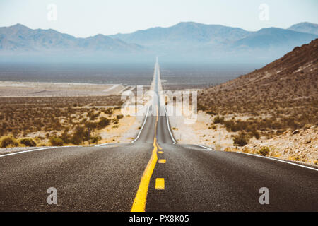 Classic panorama view of an endless straight road running through the barren scenery of the American Southwest with extreme heat haze in summer - Stock Photo