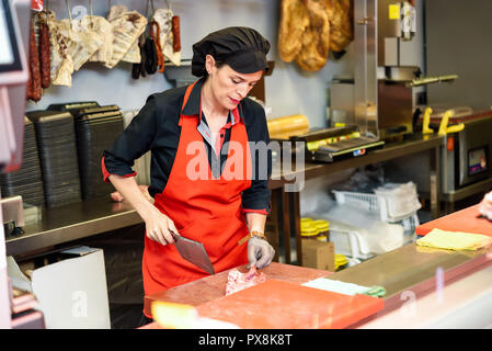 Female butcher cutting meat at counter in butchery with a ax - Stock Photo