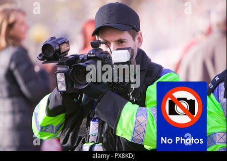 Police photographer photographing protestors at a climate change rally in London December 2008 with a no photos sign. - Stock Photo