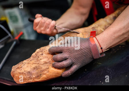 Close-up of butcher boning a ham in a modern butcher shop with metal safety mesh glove - Stock Photo