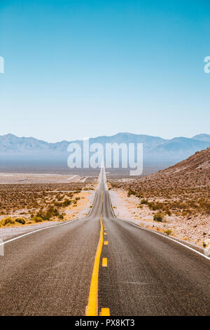 Classic panorama view of an endless straight road running through the barren scenery of the American Southwest with heat haze in summer - Stock Photo