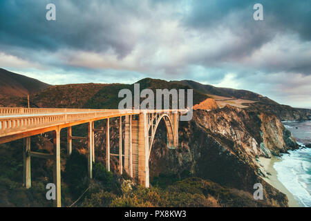 Scenic panoramic view of historic Bixby Creek Bridge along world famous Highway 1 in beautiful golden evening light at sunset with dramatic cloudscape - Stock Photo