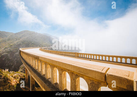 Panoramic view of historic Bixby Creek Bridge along world famous Highway 1 on a sunny day with fog in summer, Monterey County, California, USA - Stock Photo