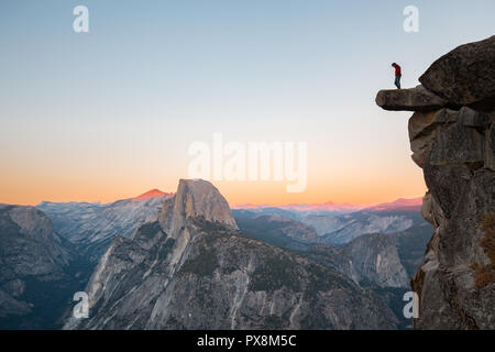 A fearless hiker is standing on an overhanging rock enjoying the view towards famous Half Dome at Glacier Point overlook in beautiful evening twilight - Stock Photo