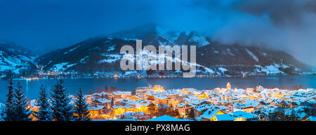 Panoramic view of Zell am See with Zeller See lake in twilight during blue hour at dusk in winter, Salzburger Land, Austria - Stock Photo