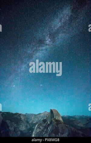 Panoramic view of beautiful starry night sky with Milky Way above Half Dome peak illuminated by full moon in summer, Yosemite National Park, Californi - Stock Photo