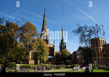 The spires of Holy Trinity Church and Coventry Cathedral as viewed from Trinity Street in Coventry city centre UK - Stock Photo