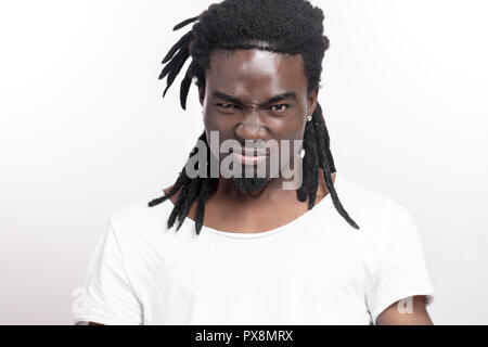 screaming young african man with dreadlocks standing isolated white background. Looking camera. - Stock Photo
