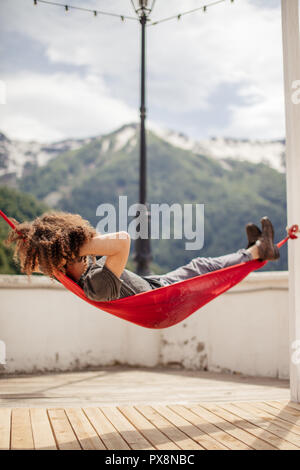 happy man relaxing lying in hammock on top of mountain. Summer vacation travel lifestyle concept - Stock Photo