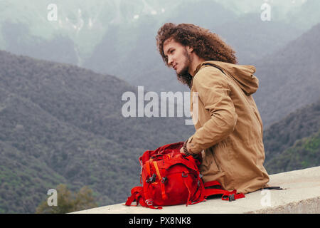 man Packing Backpack for hiking with mountains on background - Stock Photo