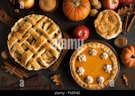 Thanksgiving pumpkin and apple various pies, top view. Fall traditional homemade apple and pumpkin pie for autumn holiday. - Stock Photo