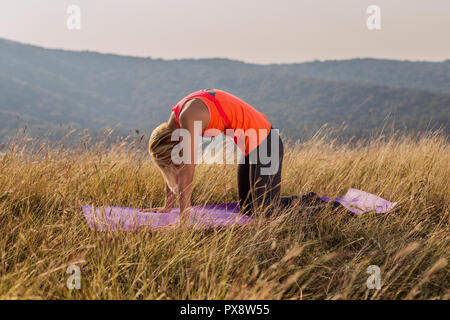 Beautiful woman doing yoga in the nature,Marjaryasana/Cat pose - Stock Photo