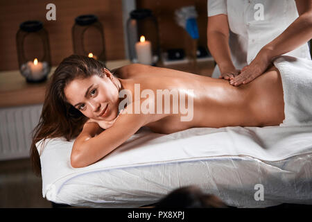 Beautiful young woman receiving body massage in spa salon - Stock Photo