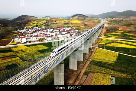 (181020) -- BEIJING, Oct. 20, 2018 (Xinhua) -- A bullet train runs on the Yangxian section of Xi'an-Chengdu high-speed railway line in northwest China's Shaanxi Province, March 21, 2018. If you came to Beijing, capital of China, 40 years ago, you were probably struck by the 'sea of bicycles' on streets, a unique phenomenon earning China the title 'kingdom of bicycles'. At that time, ordinary Chinese could not afford cars and few people could travel by air, let alone frequent long-distance travelling. Trains, the most commonly means of transportation then, were always jam-packed in the stuffy - Stock Photo