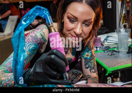 Skibbereen, West Cork, Ireland. 20th Oct, 2018. Tattooist Jen Danger from Canada tattoos the leg of Leah Grobbelaar from Drimoleague during the tattoo show. The show has been attended by many tattooists from across Ireland and the North. The event finishes tomorrow. Credit: Andy Gibson/Alamy Live News. - Stock Photo