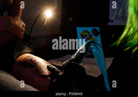 Skibbereen, West Cork, Ireland. 20th Oct, 2018. Sammi Ville from Cork tattos the leg of Lisa Timmis from Bantry during the tattoo show. The show has been attended by many tattooists from across Ireland and the North. The event finishes tomorrow. Credit: Andy Gibson/Alamy Live News. - Stock Photo