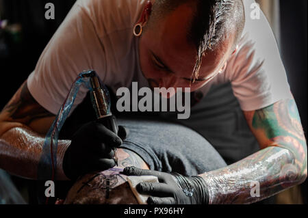 Skibbereen, West Cork, Ireland. 20th Oct, 2018. A tattooist tattos the back of a head during the tattoo show. The show has been attended by many tattooists from across Ireland and the North. The event finishes tomorrow. Credit: Andy Gibson/Alamy Live News. - Stock Photo