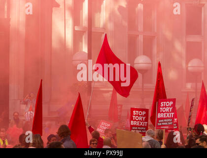 UK. 20th Oct, 2018. Red flags and placards saying 'Stop Tory Brexit' are waved against a backdrop of red smoke from flares let off during the People's Vote March against Brexit on 20th October 2018. Organisers claim over 500,000 participants took part in the event. They were campaigning for a referendum of the final terms of the United Kingdom's withdrawal from the European Union Credit: Stephen Taylor/Alamy Live News - Stock Photo