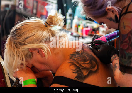 Skibbereen, West Cork, Ireland. 20th Oct, 2018. A customer finds it difficult to take the pain whilst having a tattoo done at the show. The show has been attended by many tattooists from across Ireland and the North. The event finishes tomorrow. Credit: Andy Gibson/Alamy Live News. - Stock Photo