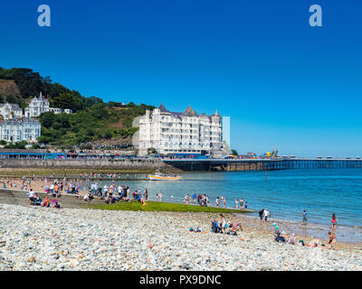 26 July 2018: Llandudno, Conwy, UK - Llandudno beach on a hot summer day, and the Grand Hotel. In the foreground is the pebble sea defence. - Stock Photo