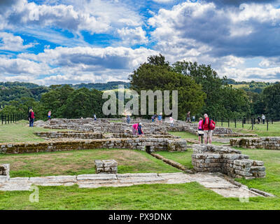 11 August 2018: Tourists viewing the excavated ruins of Chesters Roman Fort, Hadrian's Wall, Northumberland, UK - Stock Photo