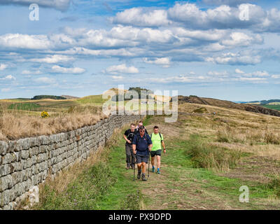 11 August 2018: Hadrian's Wall, Northumberland - Group of male hikers with walking poles walking on the Hadrians' Wall path at Walltown Crags on a war - Stock Photo