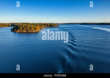 Some of the 30,000 islands of the Stockholm Archipelago, viewed from the deck of a cruise liner approaching the port, just after sunrise. - Stock Photo