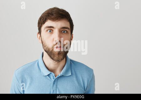 You must be joking. Portrait of confused cute bearded guy, standing with doubtful and questioned expression, moving jaw and looking with popped eyes at camera while posing over gray background - Stock Photo