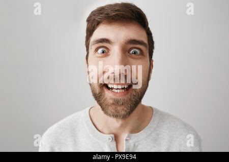 Close-up portrait of funny bearded guy making faces at camera, smiling and acting like crazy, staring with popped eyes over gray background. Man mimics popular character from scary movie - Stock Photo