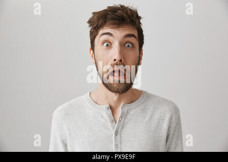 What happened yesterday, how much I drank. Portrait of funny weird man with messy hair and strange expression, being clueless and questioned, looking with lifted eyebrows at something surprising - Stock Photo