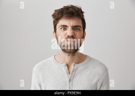Portrait of funny weird guy with messy hair and beard making faces, puckering eyebrows and sulking, standing over gray background with offended or irritated expression, losing his temper - Stock Photo