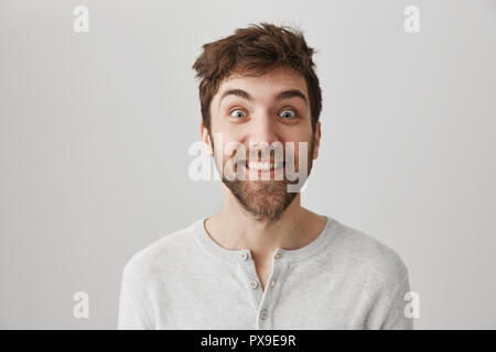 Funny and crazy bearded guy with messy hair and popped eyes, smiling and staring at camera, standing against gray background. Obsessed man stalks his ex-girlfriend. Student played games all night - Stock Photo