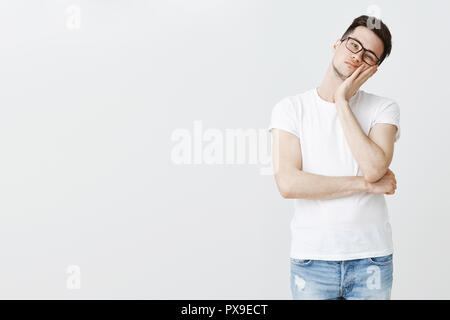 Studio shot of bored indifferent handsome young man leaning face on palm from boredom wasting time watching boring tv show posing on right side of copy space in glasses over gray wall - Stock Photo