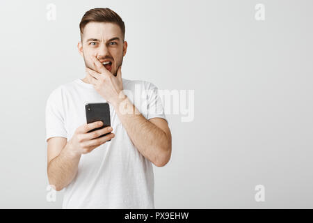 Shocked stunned handsome guy opening up terrible photo of ex-girlfriend shouting from dislike and surprise covering opened mouth and frowning staring intense holding smartphone in hand - Stock Photo