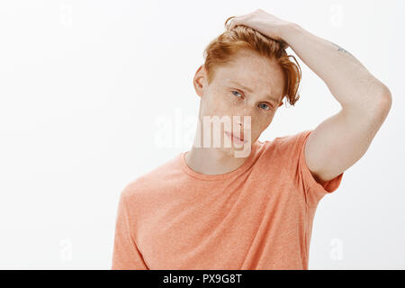 Young male student with red hair and freckles gazing at mirror and touching haircut, thinking to change hairstyle, gazing calm and cool at camera, standing confident over gray background - Stock Photo
