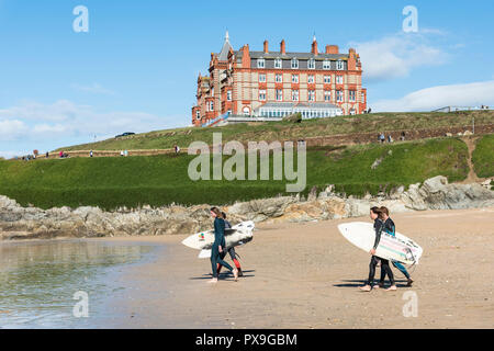 A group of surfers carrying their surfboards walking down to the sea at Fistral Beach in Newquay in Cornwall. - Stock Photo