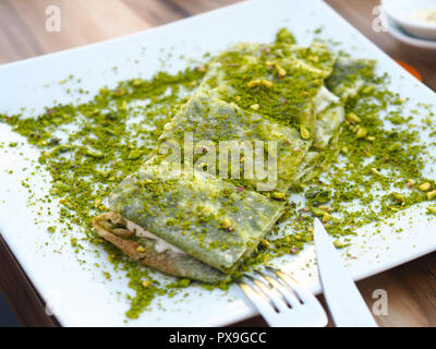 katmer dessert of Turkey Gaziantep region. Prepared with thin dough dessert with ice cream and green pistachio. - Stock Photo