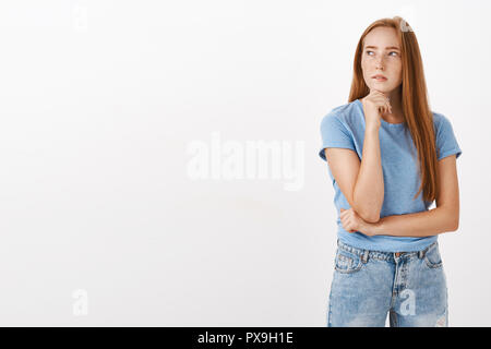 Portrait of thoughtful concentrated cute and feminine woman with long red hair and freckles turning left squinting supporting head with fist while thinking making decision or being doubtful - Stock Photo