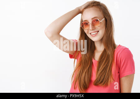 Shy and tender charming redhead lady with freckles in trendy sunglasses and pink blouse combing hair behin with hand on head and smiling friendly at camera posing over white background - Stock Photo