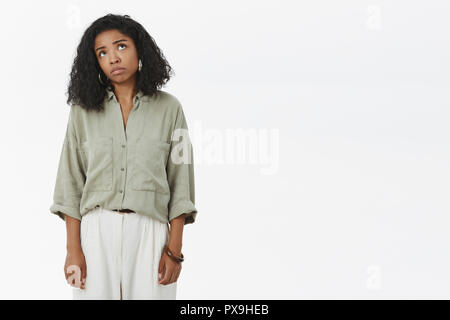 Unlucky gloomy girl thinks god playing tricks, complaining on unfair life standing displeased and unhappy looking up with sad face stooping being pessimistic posing over gray background - Stock Photo