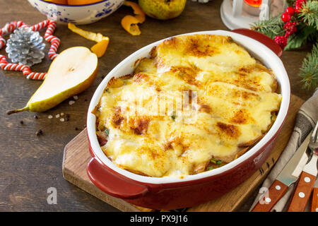 Potato gratin with pear, raclette cheese, and bacon on a festive Christmas table.Traditional french cuisine. Copy space. - Stock Photo